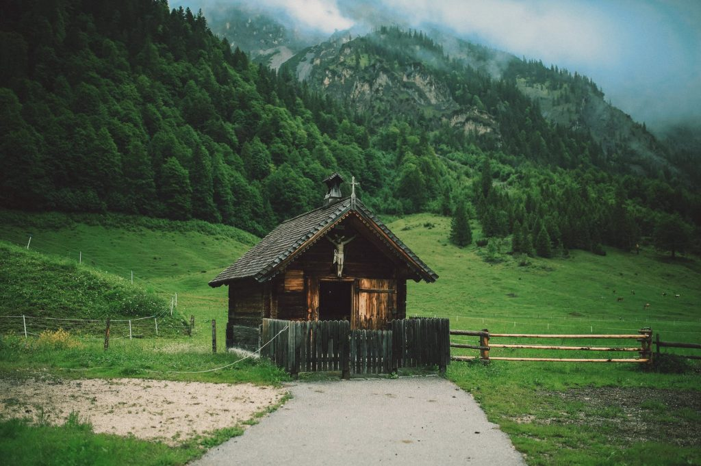 brown wooden house surrounded by grass
