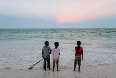 ethnic boys standing on seashore at sunset